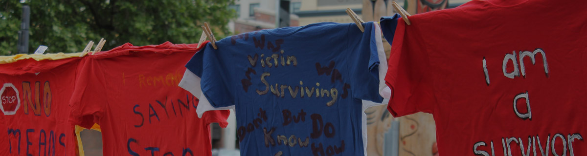 t-shirts hang on a line with text written on them saying various things that survivors wanted to write about: