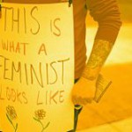 A person stands holding a plackard, declaring their pro-feminism ideology.