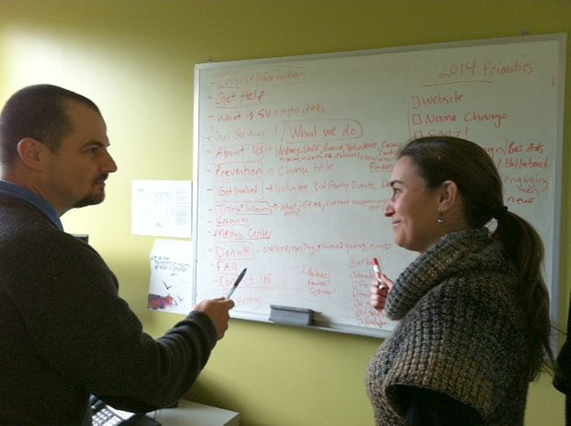 Sherwin and Lenore look over proposed website design on the whiteboard