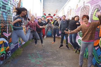 Youth Team and Community Partners Jumping for Joy on site at the Community Mural they co-created