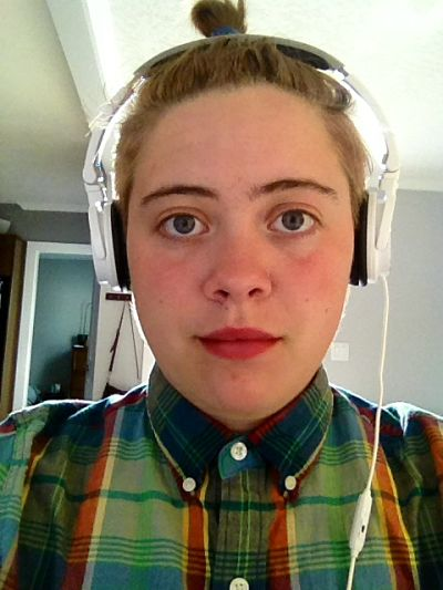 Eunice with headphones and green plaid shirt at work