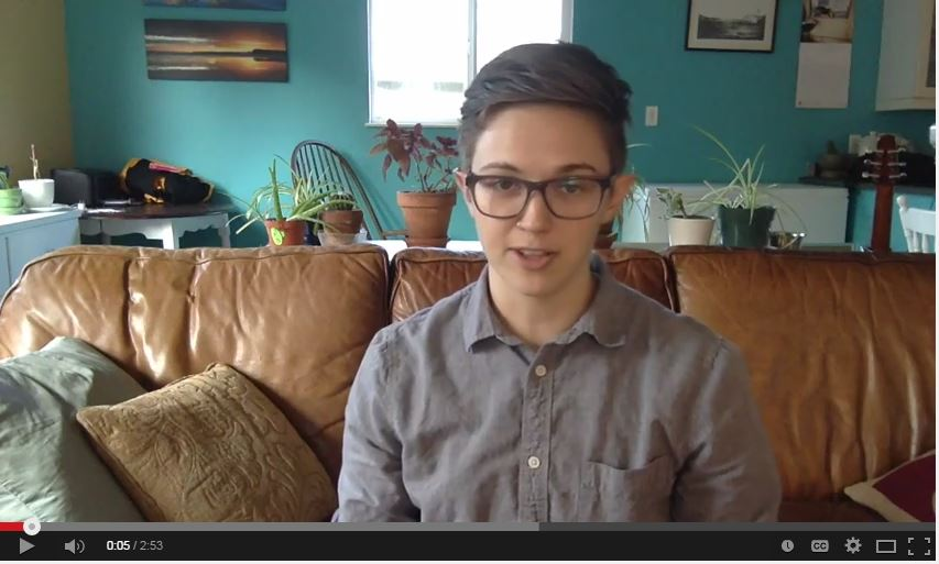 Alyx MacAdams, Trans Inclusion Coordinator, sitting on a couch for vlog update