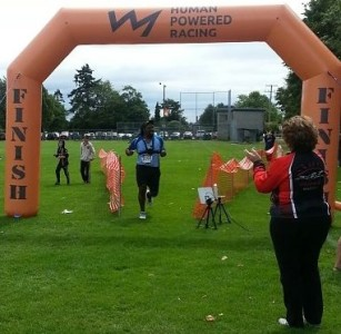 Participant crossing the finish line at the Tri of Compassion