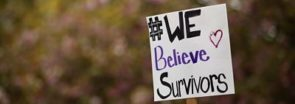 "A sign that says ""#We Believe Survivors"""
