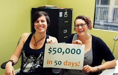 "Two co-workers hold up a sign that says ""$50,000 in 50 Days!"""
