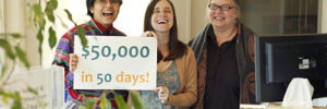 """Three co-workers hold up a sign that says """"$50,000 in 50 Days!"""""""