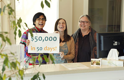 "Three co-workers hold up a sign that says ""$50,000 in 50 Days!"""