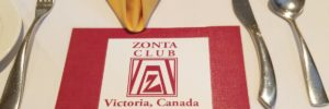 """cutlery placed on a table ready for dinner service with a gold napkin at the top and instead of a plate, it is a red and white plaque saying, """"Zonta club of Victoria"""""""