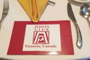 "cutlery placed on a table ready for dinner service with a gold napkin at the top and instead of a plate, it is a red and white plaque saying, ""Zonta club of Victoria"""