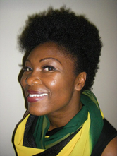 Nichola smiling wearing a bright yellow and green scarf.