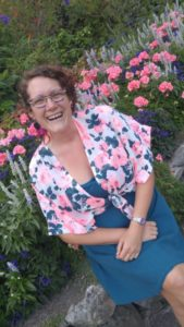 Tanille sitting down on a flowerbed ledge , smiling, wearing colourful pink and blue dress and blouse.