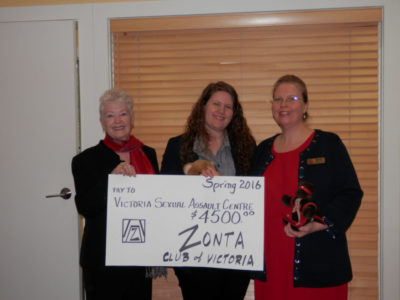 Three women standing and smiling. They are holding a large cheque from Zonta presenting it to VSAC.