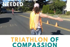 A person stand beside a road and directs a runner who is participating in a Triathlon. Volunteers Needed. Triathlon of Compassion, June 24, 2018